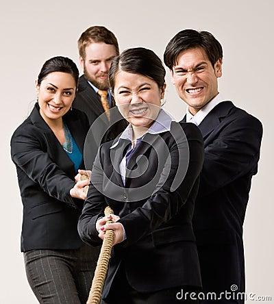Groep medewerkers die kabel in touwtrekwedstrijd trekken