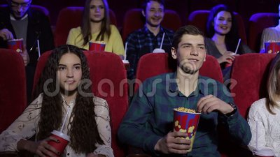 Groep tienervrienden bij de bioskoop die op een film letten en popcorn eten stock footage
