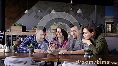 Groep van vier vrienden die bij het restaurant zitten samen en digitaal gadget gebruiken Twee knappe mensen en twee die glimlache stock video