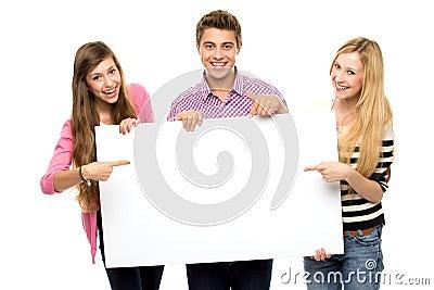 Groep vrienden die leeg aanplakbiljet houden
