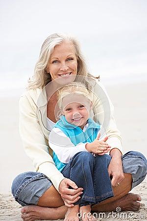 Großmutter und Enkelin, die auf Strand sitzen