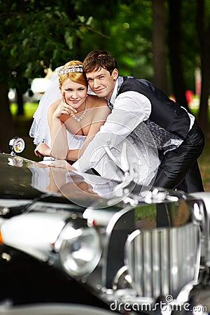Groom adn bride about retro limousine