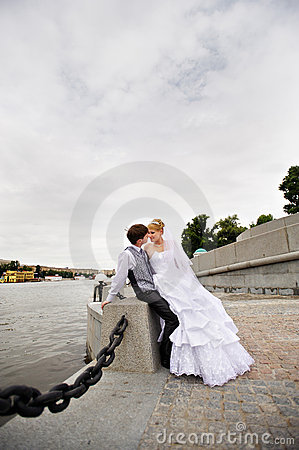 Groom adn bride for walk on embankment river