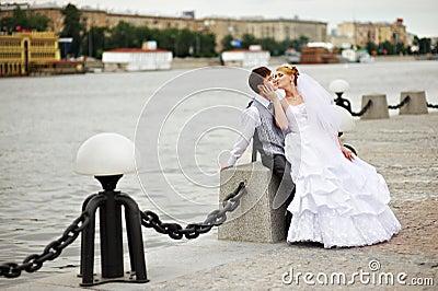 Groom adn bride for walk on embankment river