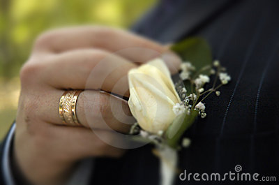 Groom arranging boutonniere flower on suit jacket