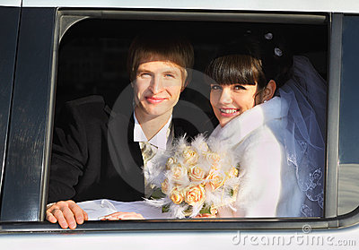 Groom and bride with bouquet sitting in limousine