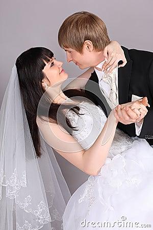 Groom and bride dance in studio