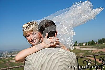 Groom and bride embracing outdoor
