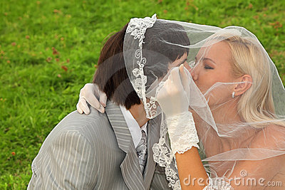 Groom and bride hidden under veil and kiss