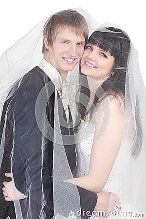 Groom and bride hide under transparent veil