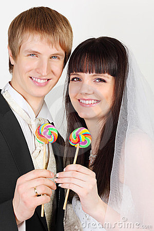 Groom and bride hold colorful lollipops