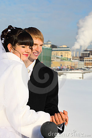 Groom and bride holding hands at winter