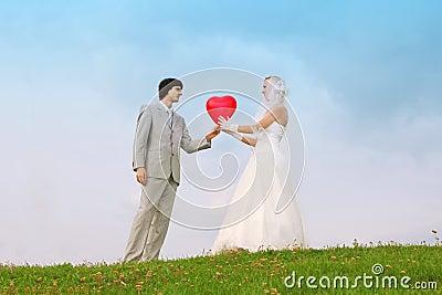 Groom and bride keep heart-shaped balloon