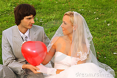 Groom and bride keep red balloon heart