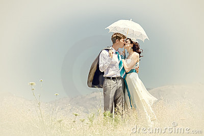 The groom and the bride kiss under summer sun