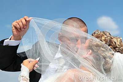 The groom and the bride kiss under a veil