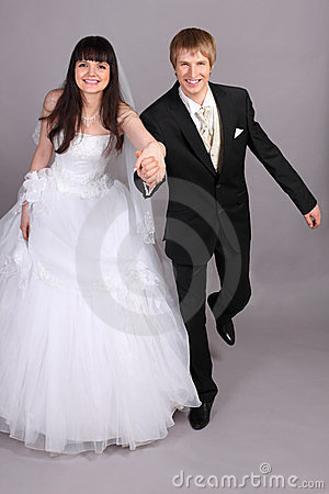 Groom and bride run in studio