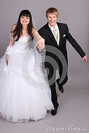 Groom and bride run in studio