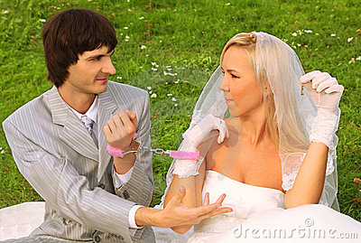 Groom and bride sitting on green grass