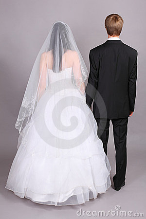 Groom and bride stand their backs to camera