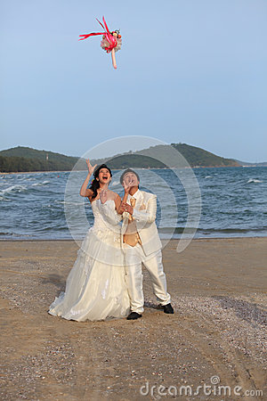 groom and bride standing with bouquet flowers at