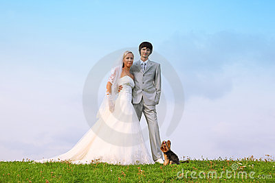 Groom and bride standing on green grass