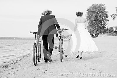 Groom and bride walk on the beach with bicycles