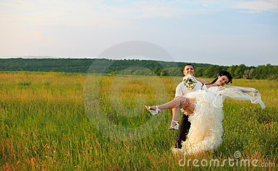 Groom is carrying bride on arms