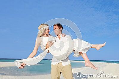 Groom Carrying Bride At Beautiful Beach Wedding