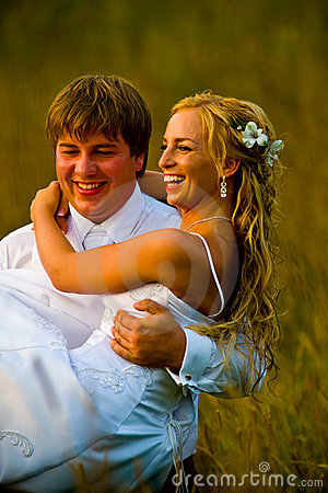 Groom carrying bride in field