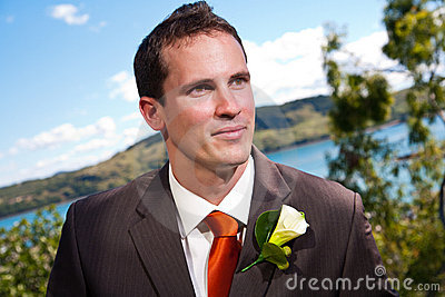 Groom and corsage with blue water behind