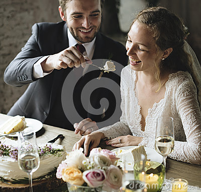 Free Groom Feeding Cake To Bride On Wedding Reception Stock Photography - 92940752