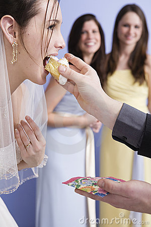 Groom feeding his bride some wedding cake.