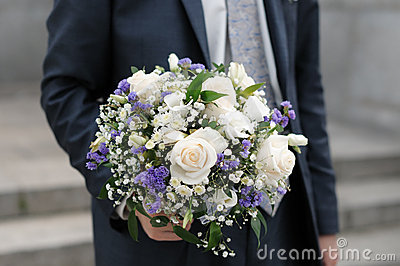 Groom holding wedding flowers bouque