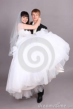 Groom holds bride in studio