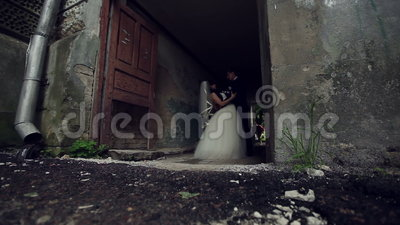 Groom kisses the bride near the old house. Meeting. newlywed. groom kisses the bride near the old house. groom kisses the bride. wedding day stock video