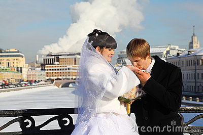 Groom kissing bride hand at winter outdoors