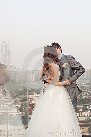 Groom kissing bride standing  ouside with huangpu river