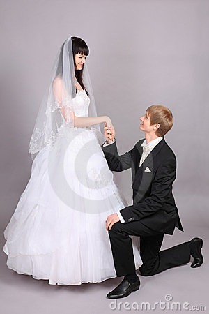 Groom kneels and holds bride hand in studio