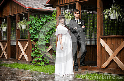 Groom and pregnant bride posing against wooden alcove