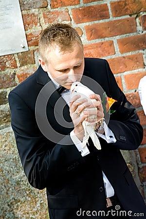 Groom releasing white dove