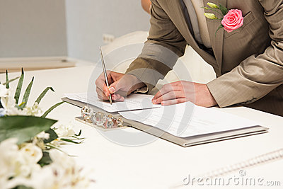 Groom signing marriage license or wedding contract