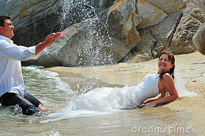 Groom splashing bride with sea water drops