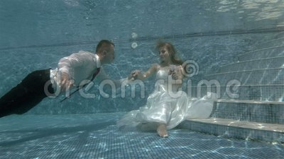 The groom swims underwater to the bride that sits at the bottom of the pool and kisses her hand. Portrait. Shooting under water. 4K, 29.97 fps stock video