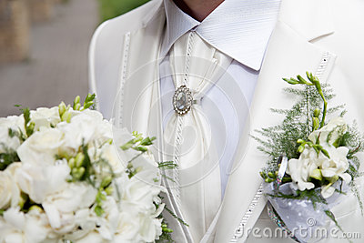 Groom in a white suit holding a wedding bouquet