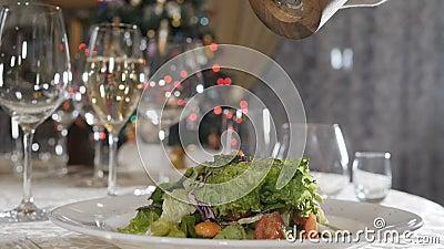 Groot zwarte peper uit de draaiende peper die langzaam op de salade valt Dranking met kerstverlichting, knipperend stock videobeelden