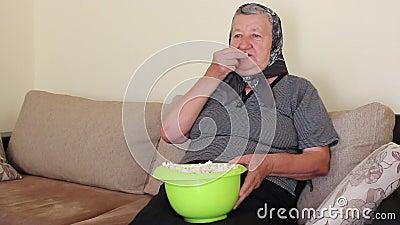 Grootmoeder die Popcorn van de Kom eten stock videobeelden