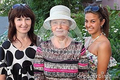 Grootmoeder, moeder, dochter dichtbij plattelandshuisje