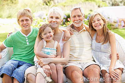 En kleinkinderen die in tuin ontspannen die bij camera glimlachen