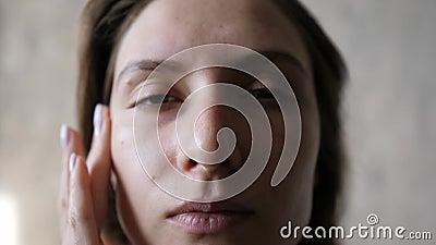 Gros plan hydratant de la peau du visage Une fille caucasienne applique de la crème naturelle, frotte la peau avec les doigts clips vidéos